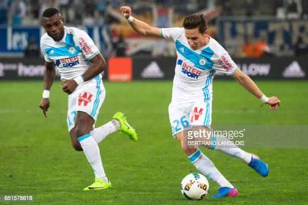 Olympique de Marseille's French midfielder Florian Thauvin kicks the ball next to Olympique de Marseille's Cameroonian defender Henri Bedimo during...