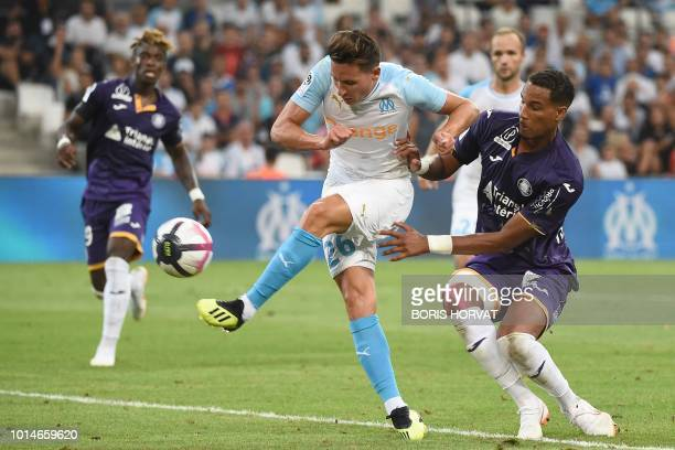 Olympique de Marseille's French midfielder Florian Thauvin shoots and scores as he vies with Toulouse's French defender Christopher Jullien during...