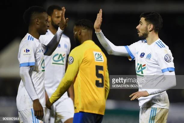 Olympique de Marseille's French midfielder Morgan Sanson is congratulated by teammates after scoring a goal during the French Cup football match...