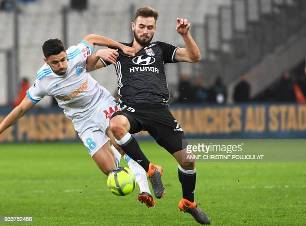 Olympique de Marseille's French midfielder Morgan Sanson vies with Lyon's French midfielder Lucas Tousart during the French L1 football match...