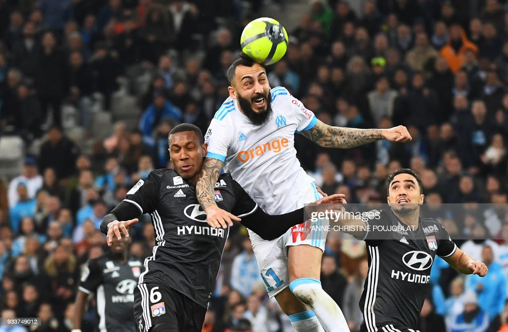 TOPSHOT - Olympique de Marseille's Greek forward Konstantinos Mitroglou (R) vies with Lyon's Brazilian defender Marcelo (L) during the French L1 football match Marseille (OM) vs Lyon (OL) on March 18, 2018 at the Velodrome stadium in Marseille, southern France. /