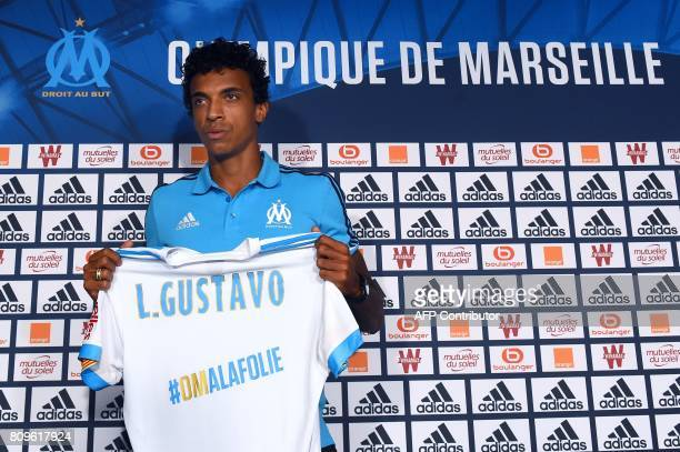 Olympique de Marseille's new Brazilian midfielder Luiz Gustavo poses with his jersey during his presentation to the club at a press conference on...