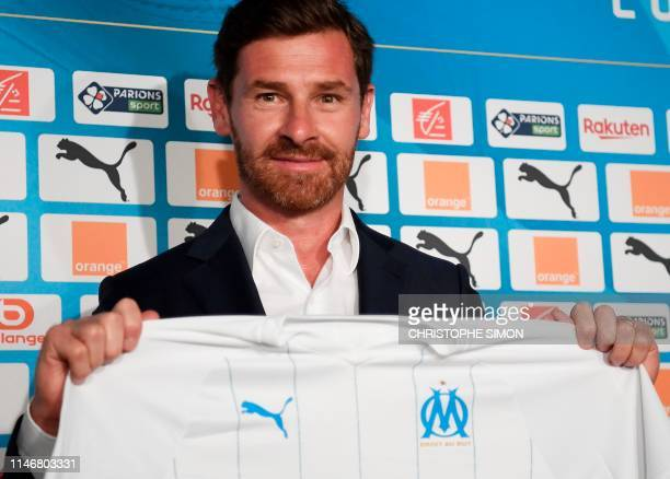 Olympique de Marseille's new coach Portuguese Andre Villas-Boas poses with a team jersey during his official presentation to the press on May 29,...