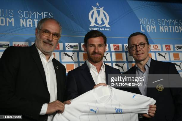 Olympique de Marseille's new coach Portuguese Andre VillasBoas poses with a team jersey with the club's president JacquesHenri Eyraud and sport...
