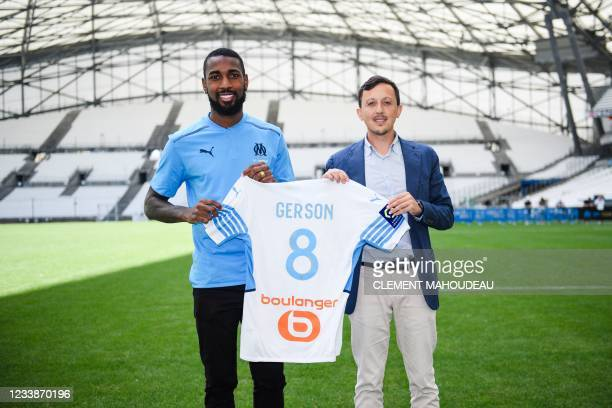 Olympique de Marseille's newly recruited Brazilian midfielder Gerson Santos da Silva poses for pictures holding his jersey with Marseille's Spanish...