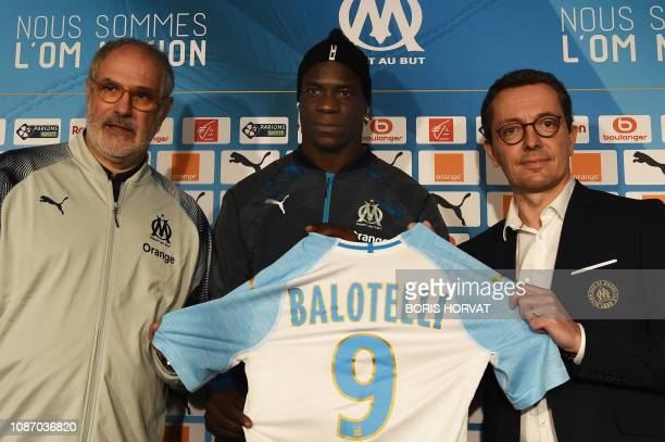 Olympique de Marseille's newly recruited Italian forward Mario Balotelli poses with his new jersey flanked by the club's president Jacques Henry...