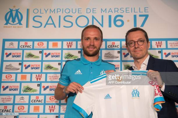 Olympique de Marseille's newly recruited player Valere Germain holds his new jersey next to Olympique de Marseille French president JacquesHenri...