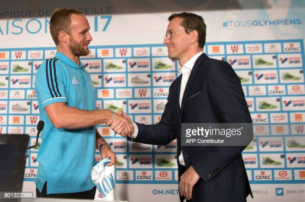 Olympique de Marseille's newly recruited player Valere Germain shakes hands with Olympique de Marseille French president JacquesHenri Eyraud during...