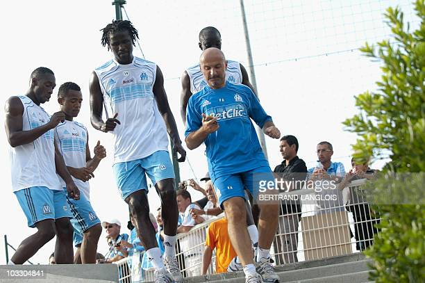 Olympique de Marseille's players Senegalese Leyti N'Diaye and coach assistant Italian Antonio Pintus run next to their fans during a training session...