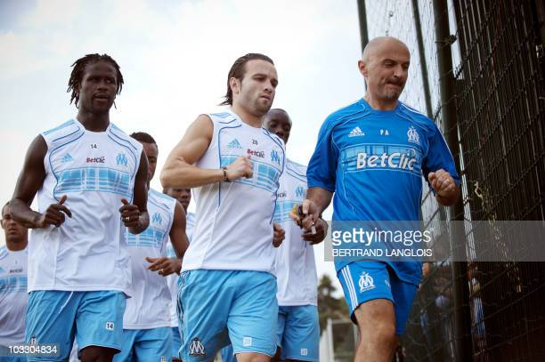 Olympique de Marseille's players Senegalese Leyti N'Diaye and French Mathieu Valbuena and coach assistant Italian Antonio Pintus run during a...