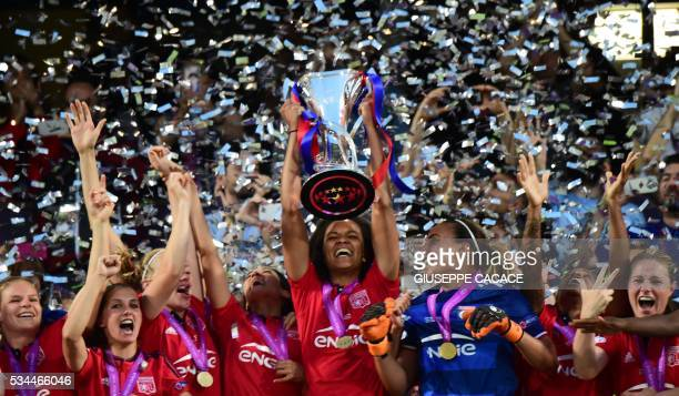 Olympique Lyonnais' captain Wendie Renard holds the trophy next to teammate goalkeeper Sarah Bouhaddi to celebrate their victory after winning the...