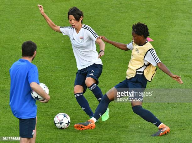 Olympique Lyonnais' French defender Saki Kumagai vies with teammate French defender Kadeisha Buchanan during a training session at the Valeriy...