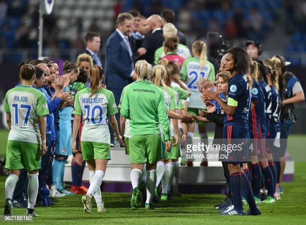 Olympique Lyonnais' French defender Wendie Renard and teammates applaud Wolfsburg player heading to the podium at the end of the UEFA Women's...