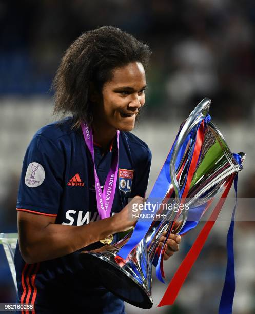 Olympique Lyonnais' French defender Wendie Renard holds the trophy as she celebrates their victory after the UEFA Women's Champions League final...