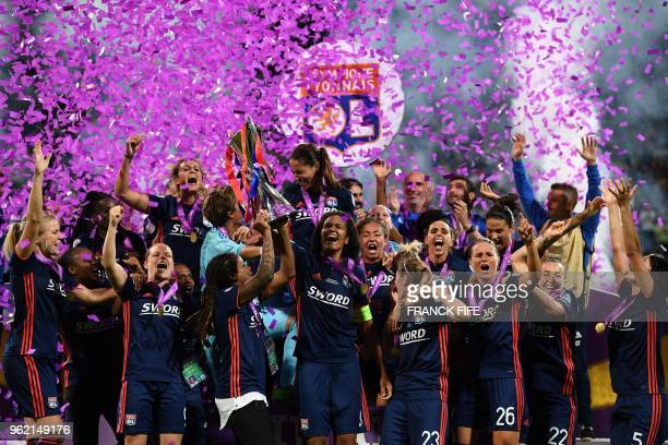 TOPSHOT Olympique Lyonnais' French defender Wendie Renard holds the trophy with teammates as they celebrate their victory after the UEFA Women's...