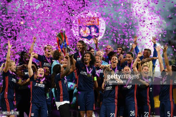 Olympique Lyonnais' French defender Wendie Renard holds the trophy with teammates as they celebrate their victory after the UEFA Women's Champions...