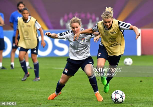 Olympique Lyonnais' French midfielder Amandine Henry vies with teammate Norwegian forward Ada Hegerberg during a training session at the Valeriy...