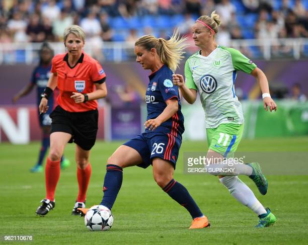 Olympique Lyonnais' French midfielder Amandine Henry vies with Wolfsburg's German forward Alexandra Popp past Czech referee Jana Adamkova during the...