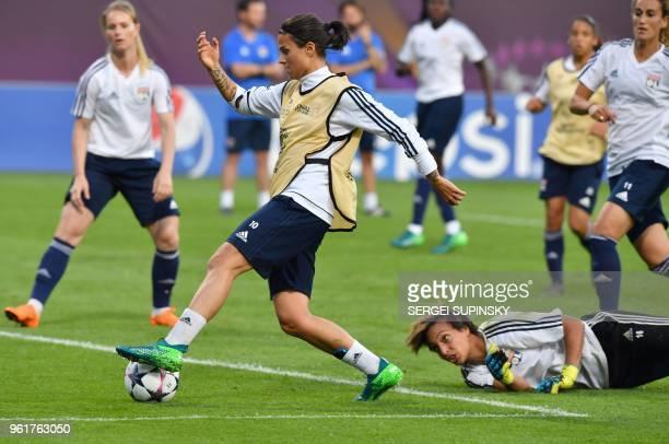 Olympique Lyonnais' German midfielder Dzsenifer Marozsan controls the ball past teammate French goalkeeper Sarah Bouhaddi during a training session...