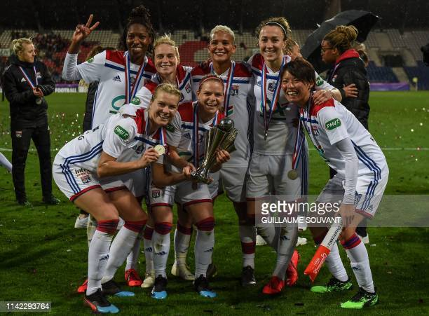 Olympique Lyonnais' players pose for a picture as they celebrate after winning the French Cup final women football match against Lille , on May 8 at...
