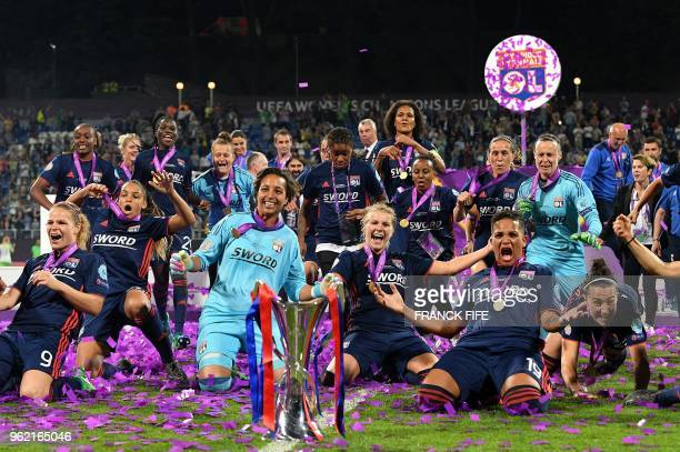 Olympique Lyonnais' players pose with the trophy as they celebrate their victory at the end of the UEFA Women's Champions League final football match...