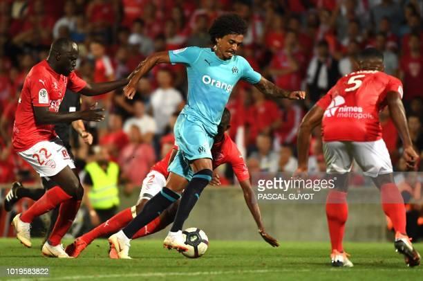 Olympique Marseille's Brazilian midfielder Luiz Gustavo vies with Nîmes' French defender Loïck Landre and Nîmes' French forward Sada Thioub during...