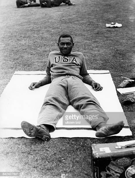 Olympische Spiele 1936 in Berlin Hochsprung Maenner David Albritton ruht sich waehrend des Wettbewerbs im Trainingsanzug aufeiner Decke auf dem Rasen...