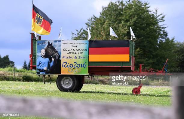 Olympische Spiele Rio 2016 Reiten Vielseitigkeit Olympiasieger Michael Jung Ein Plakat mit Glueckwuenschen und Deutschland Fahne an einem Anhaenger...