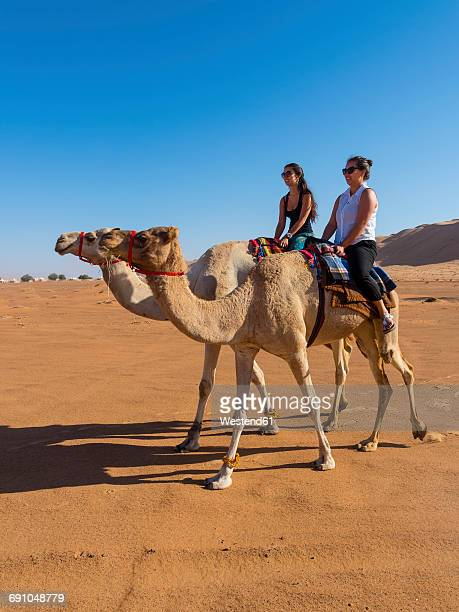 Oman, Al Raka, Rimal Al Wahiba desert, two women riding on dromedaries