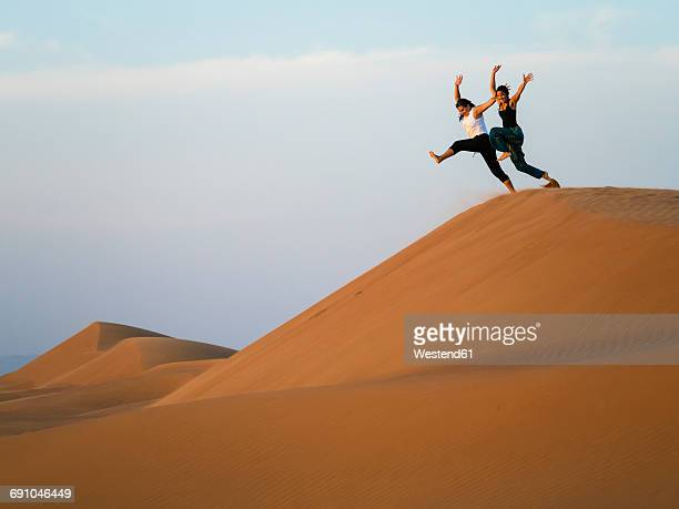 Oman, Al Raka, two young women jumping from dune in Rimal Al Wahiba desert
