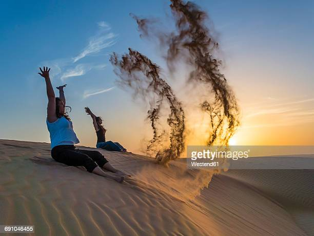 Oman, Al Raka, two young women sitting on a dune in Rimal Al Wahiba desert throwing sand in the air