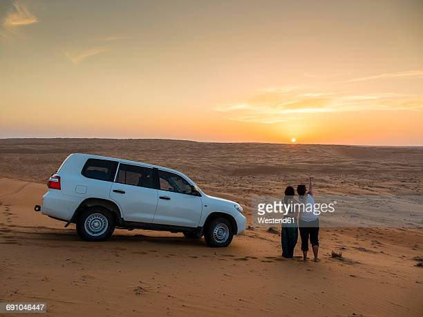 Oman, Al Raka, two young women standing besides off-road vehicle on a desert dune watching sunset