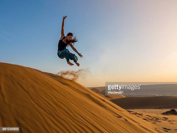Oman, Al Raka, Young woman jumping from dune in Rimal Al Wahiba desert
