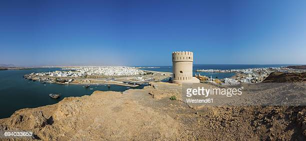 Oman, Ash Sharqiyah, Ad Daffah, view to seaport Sur and Blue Lagoon with watch tower in the foreground