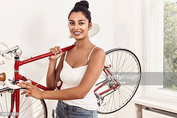oman carrying red racing cycle on her shoulder