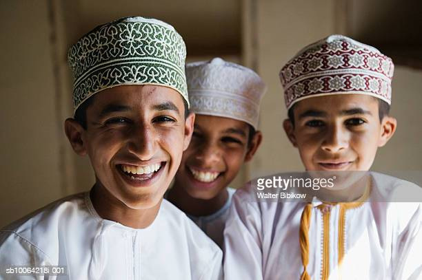 Oman, Western Hajar Mountains, Jabrin Castle, three school boys smiling, portrait