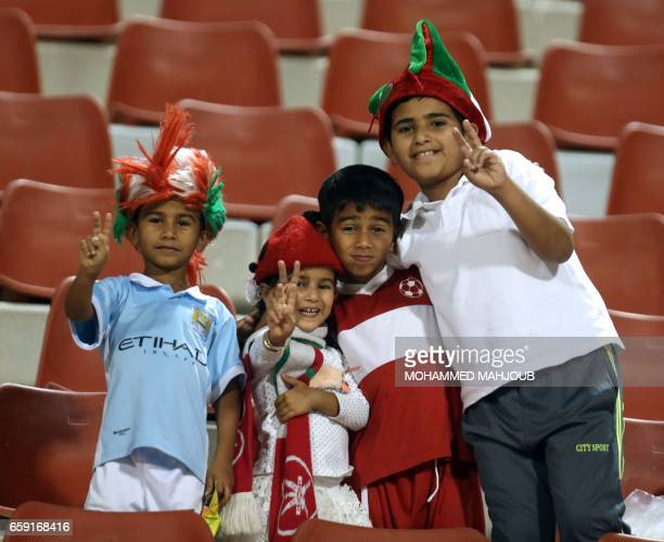 Omani children cheer during the Asian Cup qualifying football match between Oman and Bhutan on March 28 2017 at the Sultan Qabous stadium in Muscat /...