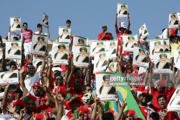 Omani fans hold portraits of Oman's Sultan Qaboos bin Said as they attend the 2014 World Cup Asian zone group B qualifying football match between...
