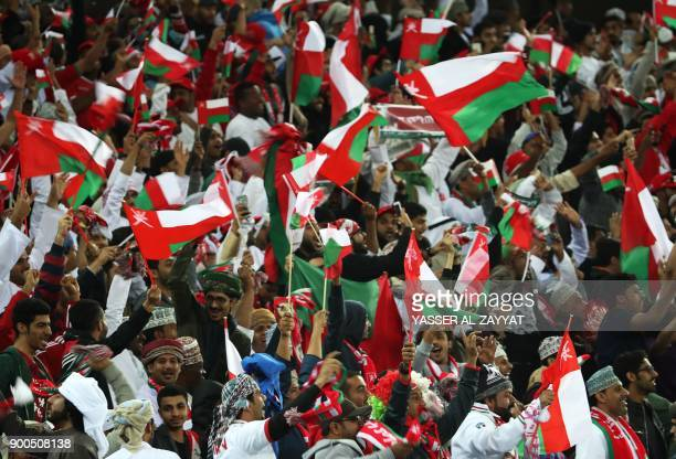 Omani fans wave their national flag as they celebrate after their national team scored a goal during the 2017 Gulf Cup of Nations semifinal football...