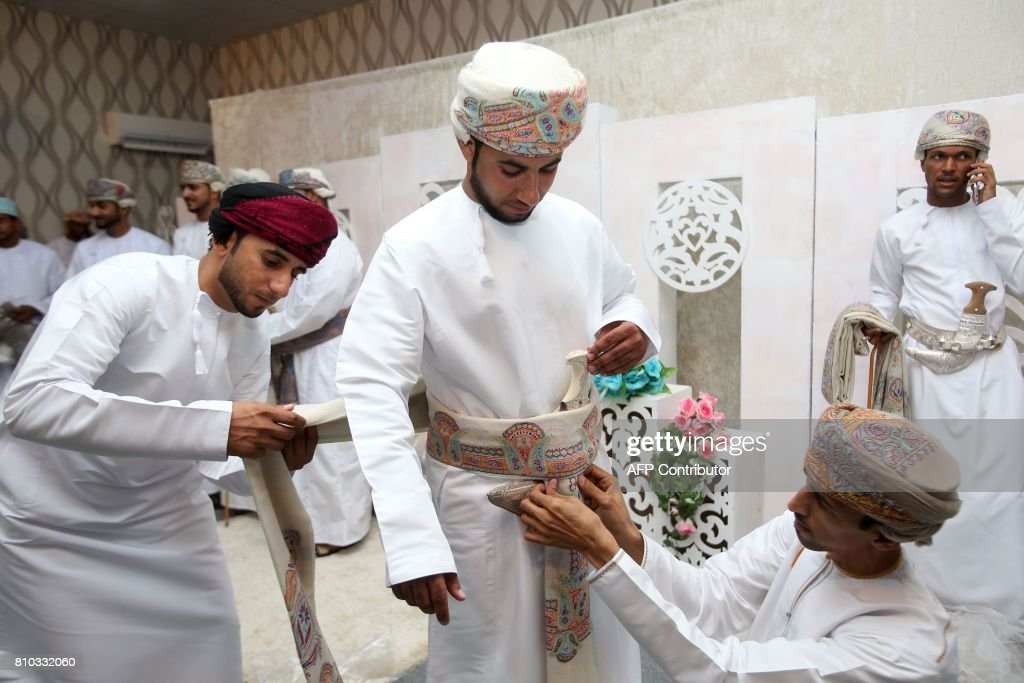 Omani grooms dress up ahead of a mass wedding ceremony of 25