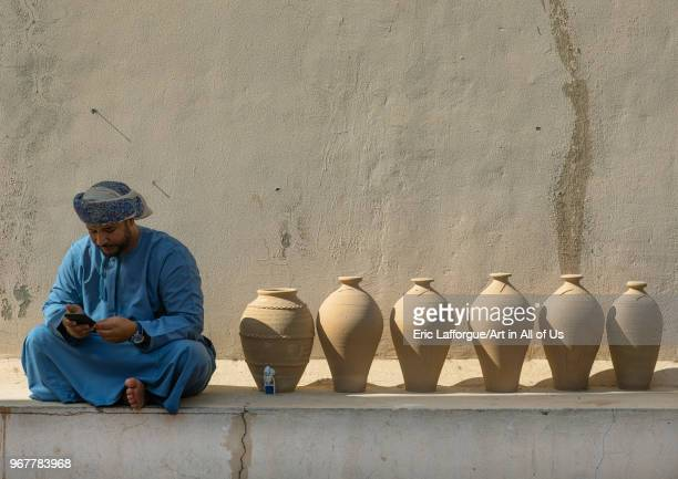 Omani man reading his mobile phone sit next to potteries Ad Dakhiliyah Region Nizwa Oman on May 11 2018 in Nizwa Oman