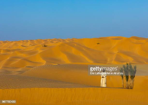 Omani man standing near a tree in the rub al khali desert Dhofar Governorate Rub al Khali Oman on May 14 2018 in Rub Al Khali Oman