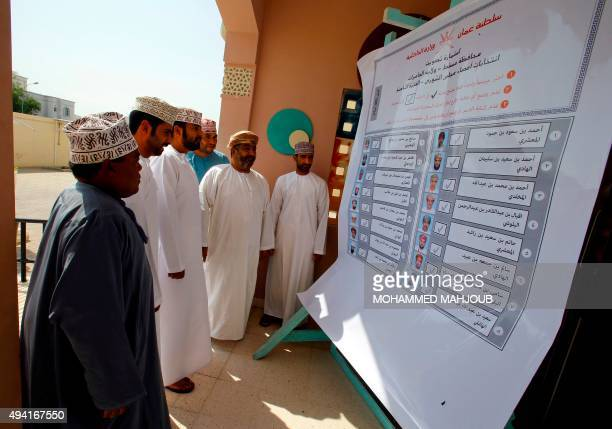 Omani men look at the list of candidates for a consultative council at a polling station in Muscat on October 25 where the longtime ruling sultan...