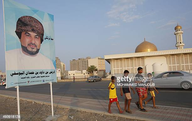 Omani men walk past an election campaign billboard in the capital Muscat on October 23 2015 ahead of the Shura Council election which will take place...