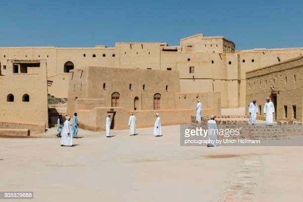 omani men walking around bahla fort, bahla, oman - loam stock photos and pictures