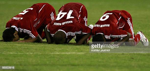Omani players Mohammed alBloshi Hassan Rabih and Hashim Saleh pray after winning against Saudi Arabia in the 19th Gulf Cup football tournament in...