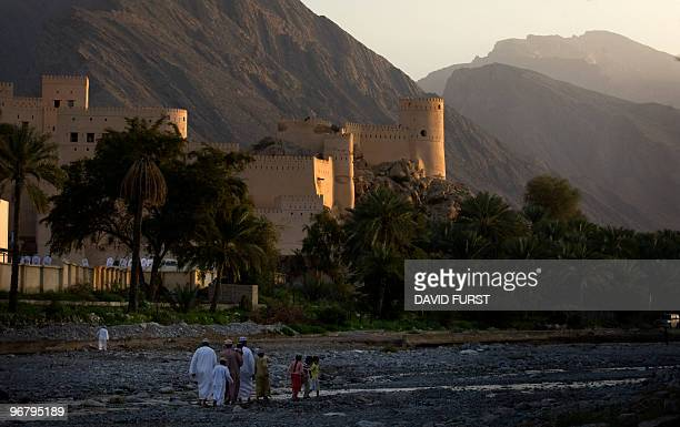 Omani villagers walk past an old castle through a riverbed in Nakhal Oman on February 17 2010 AFP PHOTO/DAVID FURST
