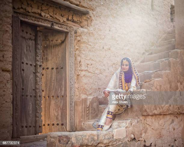 omani woman sitting on old staircase in mudbrick home - gulf of oman photos et images de collection