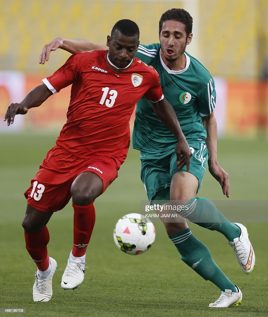 Oman's Abdul Sallam Al-Mikhaini (L) vies with Algeria's Ishak Belfodil during their friendly football game on March 30, 2015 at the Qatar Club Stadium in Doha, as part of the preparations for the second round of the 2018 World Cup's Asian leg qualifiers.
