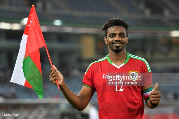 Oman's Ahmed Mubarak Obaid alMahaijri holds his national flag as he celebrates after winning the 2017 Gulf Cup of Nations semifinal football match...